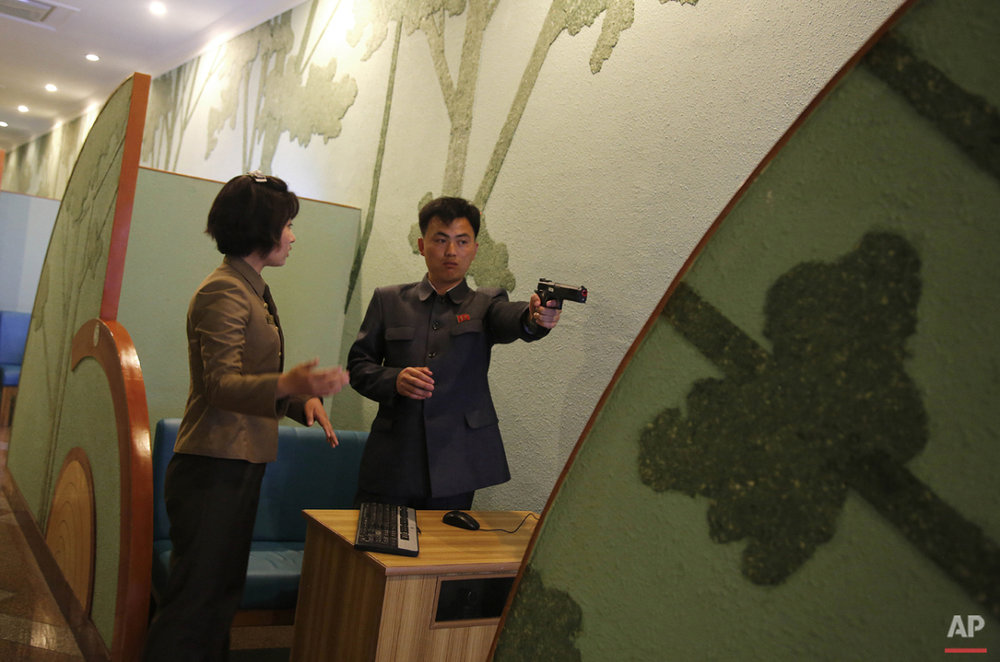 In this Monday, May 4, 2015, photo, a staff member coaches a North Korean man at a shooting arcade, one of the more popular tourists sites in Pyongyang, North Korea. (AP Photo/Maye-E Wong)