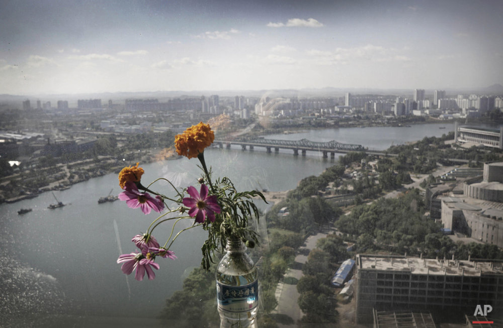 A vase of flowers, seen from a hotel window, overlooks the Taedong River, Monday, Oct. 12, 2015, in Pyongyang, North Korea. Pyongyang is the capital of North Korea. (AP Photo/Maye-E Wong)