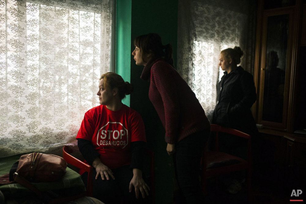 Rosario Echevarria Pedrezuela, left, her sister, right, and a housing right activist, centre, look at the police cordon the area around the apartment to evict her in Madrid, Spain, Monday, Feb. 16, 2015. The apartment occupied by Echevarria Pedrezuela, her husband Angel Echevarria Gabarri, 35, and their two children, aged 5 and 8 belongs to Bankia bank, after the previous owner was unable to continue paying the mortgage. The family occupied the foreclosed apartment ten months ago after they were evicted from their previous home. With both Echevarria Pedrezuela and her husband being unemployed and the family's sole income being a state benefit of euro 530 ($ 604), they could not afford to pay rent. Attempts to negotiate a low rent with the bank were turned down, resulting in the family's eviction by police. (AP Photo/Andres Kudacki)