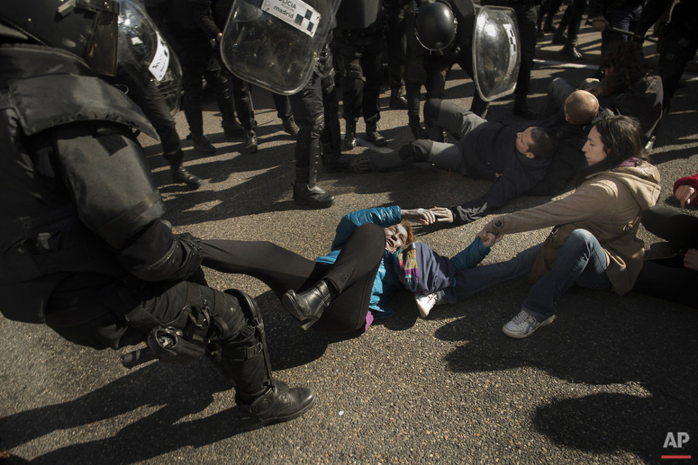 Riot Police remove housing rights activists as they tries to stop Luisa Gracia Gonzalez and her family's eviction and the demolition of their house by a forced expropriation in Madrid, Spain, Friday, Feb. 27, 2015. Madrid authorities say 11 people were arrested after several dozen protesters clashed with police who were carrying out an eviction order. A city spokeswoman said seven people were arrested for throwing gasoline at police officers, though she said the fuel was not set alight. The official spoke on condition of anonymity in keeping with city hall rules. Evictions in Spain have soared since the country's economic crisis began in 2008 and increasing numbers of people were unable to meet mortgage payments. Protesters regularly try to prevent evictions, but Friday's clash was particularly tense after a campaign to keep the family in its home. The house was expropriated for demolition as part of new urban project. Some 30 protesters tried to stop it, accusing authorities of real estate speculation. (AP Photo/Andres Kudacki)