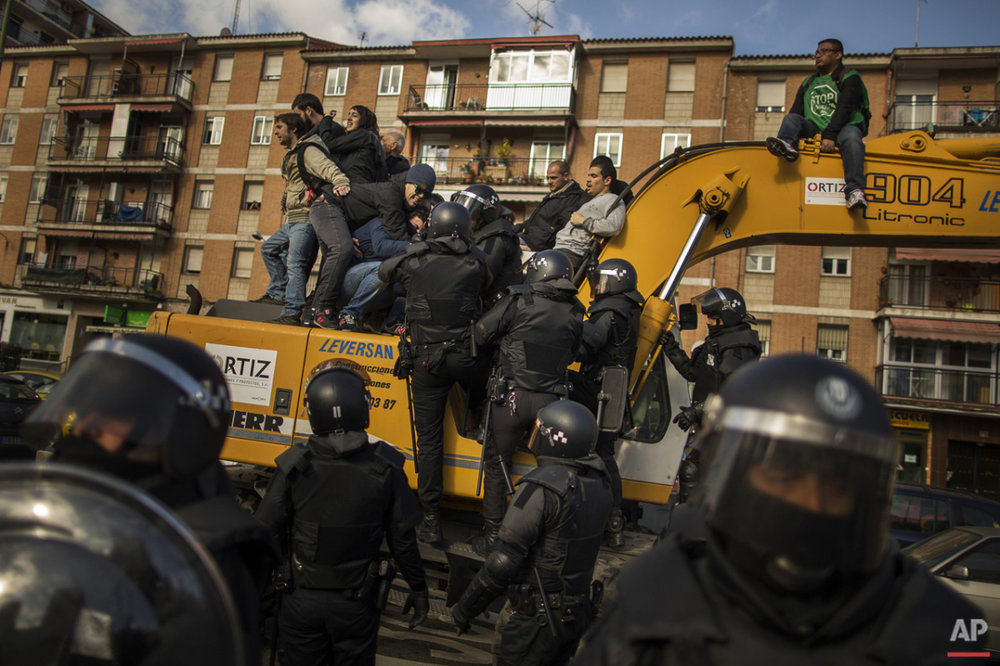 Riot Police remove a housing rights activists who claimed a bulldozer as they triy to stop Luisa Gracia Gonzalez and her family's eviction and the demolition of their house by a forced expropriation in Madrid, Spain, Friday, Feb. 27, 2015. Madrid authorities say 11 people were arrested after several dozen protesters clashed with police who were carrying out an eviction order.