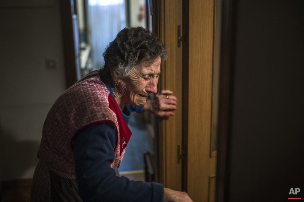 Carmen Martinez Ayuso, 85-years old, cries during her eviction in Madrid, Spain, Friday, Nov. 21, 2014. Carmen Martinez Ayuso lost her foreclosed apartment to a moneylender after she could not afford to pay her debt and the high interest rates due to her financial situation after his son lost his job. Martinez Ayuso got evicted in spite of housing right activists clash with the dozens of riot police and at least one protestor was arrested.