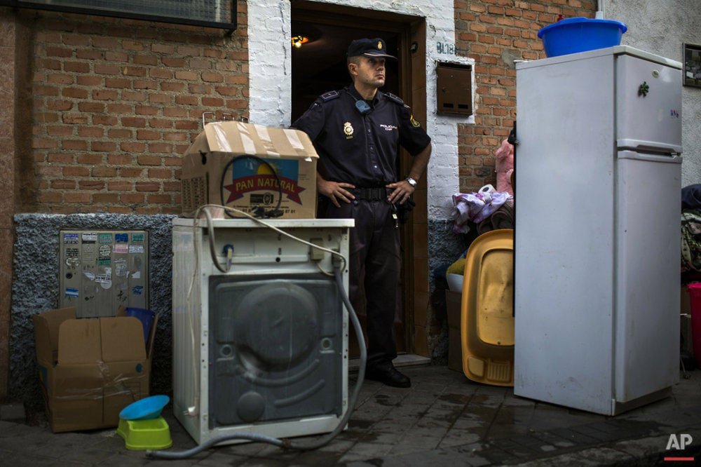 "Police block the apartment's entrance  as Amalio Barrul Gimenez' belongings lay on the street after Amalio and his family's got evicted in Madrid, Spain, Tuesday, June 24, 2014. Amalio Barrul Gimenez, , 41 years old, his wife Isabel Morales Bachiller, 35 years old, 2 month pregnant, and three children live with a low income coming from selling goods in the street and state benefits of 530 euros ($720). They occupied Bankia Bank apartment one and a half year ago and have tried to negotiate to pay a low rent but the bank demanded their eviction. The eviction was carried out in spite of the Victims' Mortgage Platform (PAH). Banners read ""Shame"" ""you are laughing and we are suffering"", ""three children in the street"", ""a pregnant woman evicted"", ""extra payment to evict people"". (AP Photo/Andres Kudacki)"