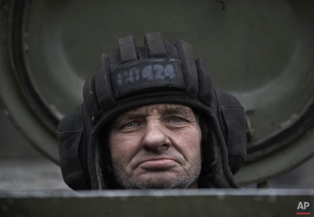 A Russia-backed separatist fighter sits in a self propelled 152 mm artillery piece, part of a unit moved away from the front lines, in Yelenovka, near Donetsk, Ukraine,Thursday, Feb. 26, 2015. (AP Photo/Vadim Ghirda)