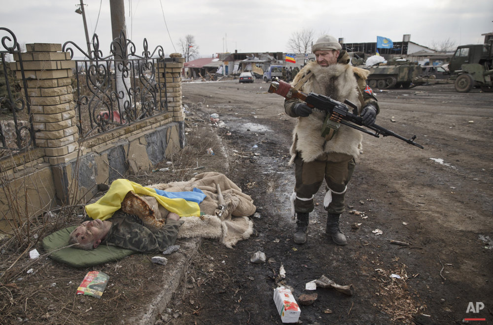 A Russia-backed rebel looks at the flag covered body of an Ukrainian serviceman in Debaltseve, Ukraine, Friday, Feb. 20, 2015. (AP Photo/Vadim Ghirda)