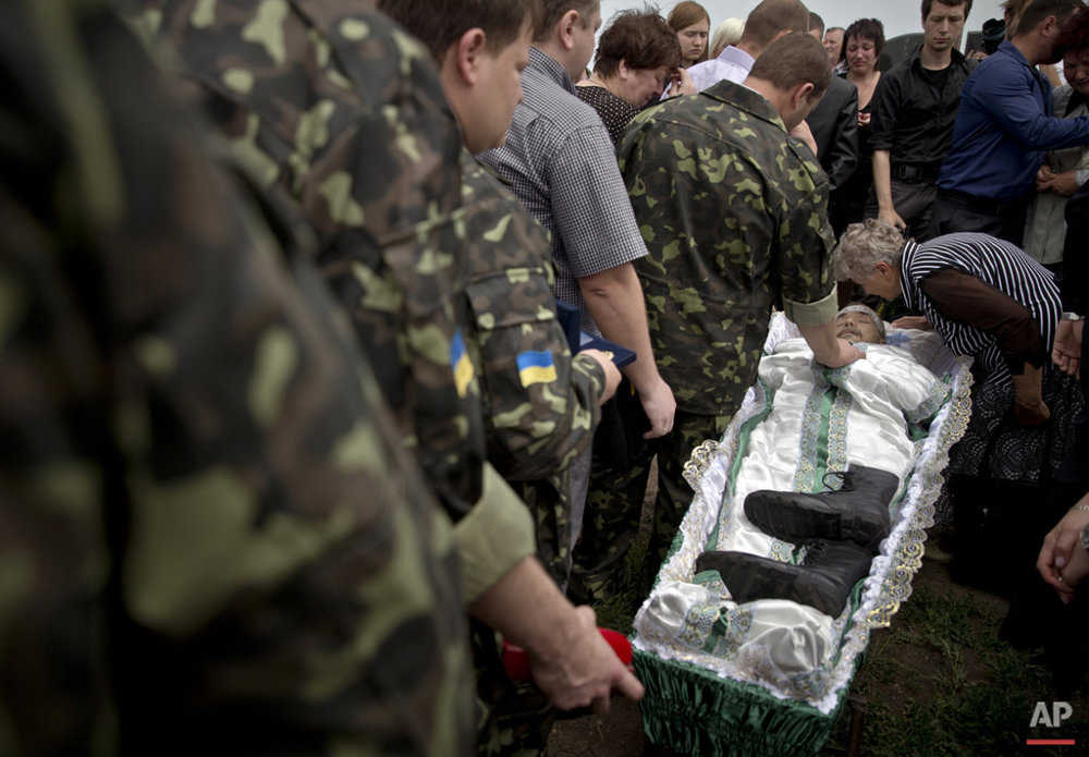 Pro-Russian rebels and relatives walk next to the coffin of Alexander Alexandrovich Gizai, a member of military-patriotic group 'Kaskad' who was killed Monday during clashes with Ukrainian troops, during his funeral in Luhansk, eastern Ukraine, Wednesday, June 4, 2014. (AP Photo/Vadim Ghirda)