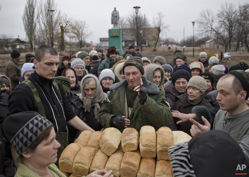 "A man speaks to a crowd of residents warning them not to push as they wait to get bread, one per person, baked by Russia-backed separatists in Chornukhyne, Ukraine, Monday, March 2, 2015. More than 6,000 people have died in eastern Ukraine since the start of the conflict almost a year ago that has led to a ""merciless devastation of civilian lives and infrastructure,"" the U.N. human rights office said Monday. (AP Photo/Vadim Ghirda)"