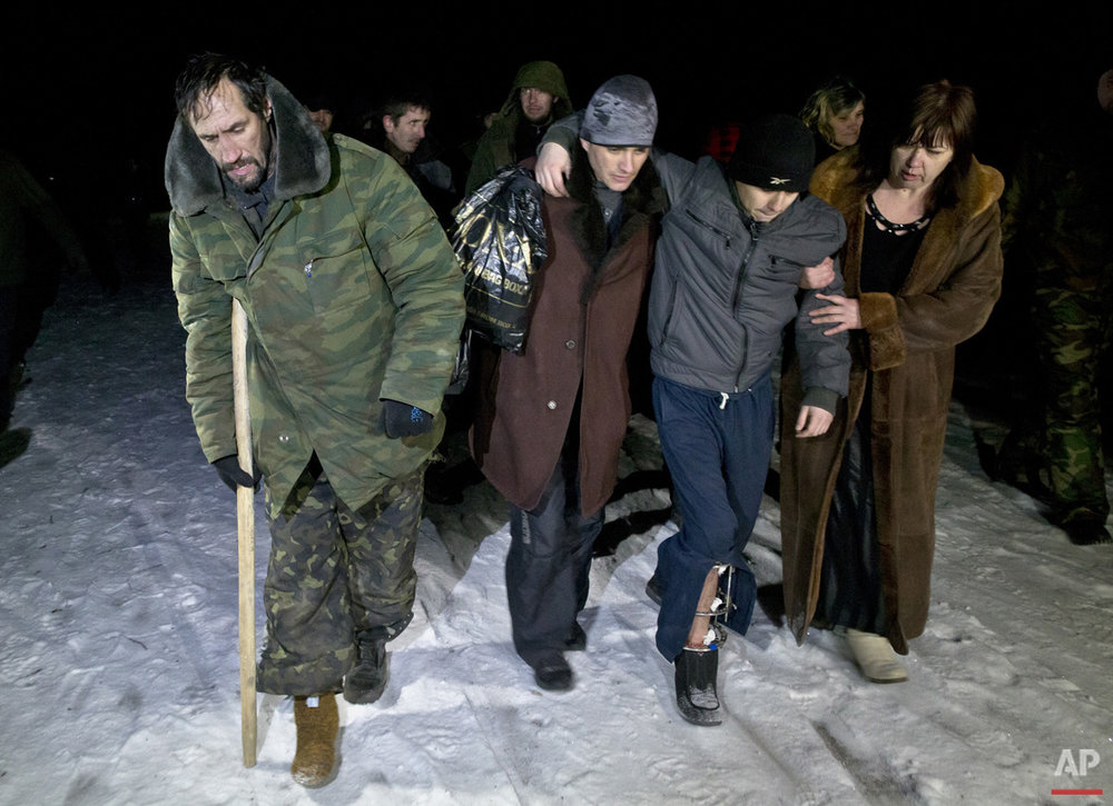 Russia-backed separatists, some injured,  walk on a snowy road in no man's land after being released by the Ukrainian military in a prisoner exchange, near Zholobok,  Ukraine, Saturday, Feb. 21, 2015. Ukrainian military and separatist representatives exchanged dozens of prisoners under cover of darkness at a remote frontline location Saturday evening. 139 Ukrainian troops and 52 rebels were exchanged, according to a separatist official overseeing the prisoner swap at a no man's land location near the village of Zholobok, some 20 kilometers (12 miles) west of Luhansk. (AP Photo/Vadim Ghirda)