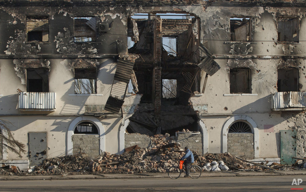 A man rides a bicycle by a destroyed building in Vuhlehirsk, Ukraine, Monday, March 9, 2015. (AP Photo/Vadim Ghirda)