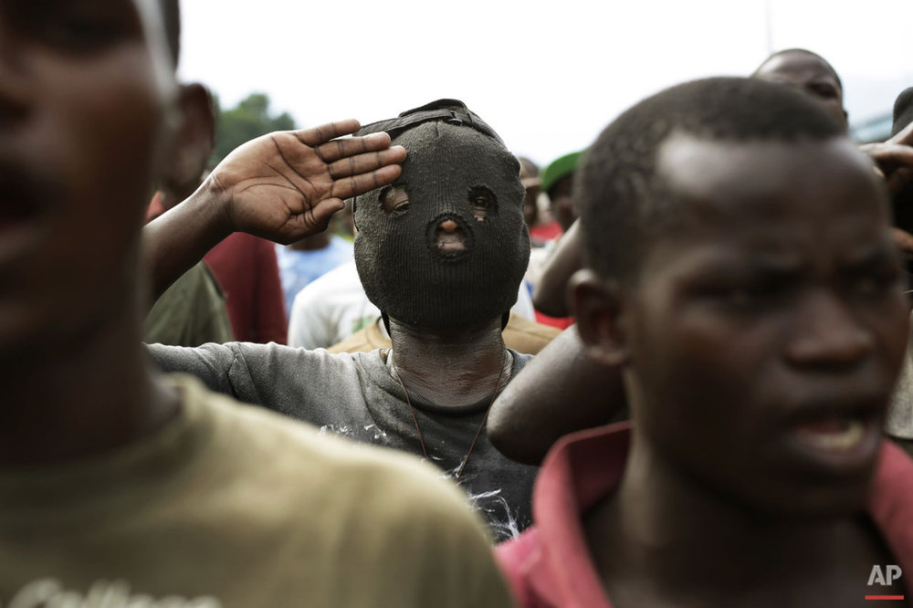 Demonstrators sing the national anthem in front of a line of riot police in the Musaga neighborhood of Bujumbura, Burundi, Friday May 1, 2015. (AP Photo/Jerome Delay)