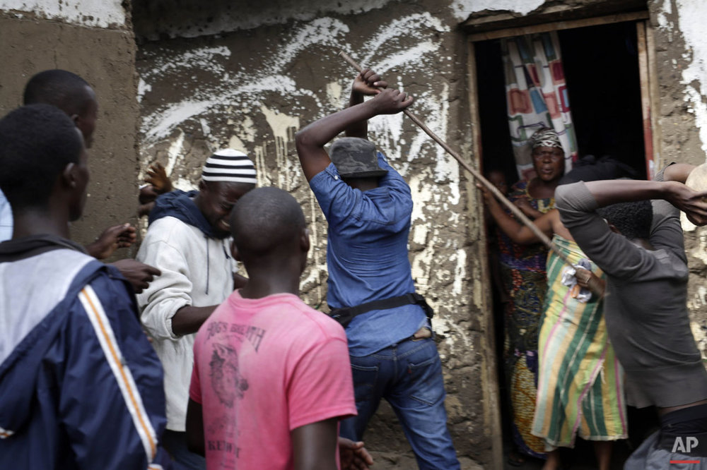 Demonstrators corner a suspected member of the ruling party's Imbonerakure youth militia at his home in the Cibitoke district of Bujumbura, Burundi, Thursday May 7, 2015. (AP Photo/Jerome Delay)