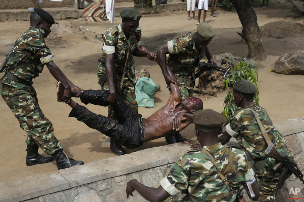 Soldiers lift a wounded suspected Imbonerakure militiaman who was attacked by demonstrators protesting against President Pierre Nkurunziza's decision to seek a third term in office in the Cibitoke district of Bujumbura, Burundi, Thursday May 7, 2015. (AP Photo/Jerome Delay)