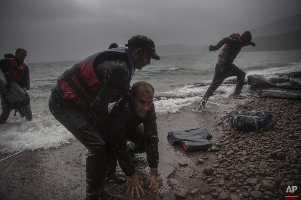 Migrants disembark from a dinghy on a beach after arriving from the Turkish coast to the village of Skala Sikaminias on the northeastern Greek island of Lesbos, on Thursday, Oct. 22, 2015. (AP Photo/Santi Palacios)