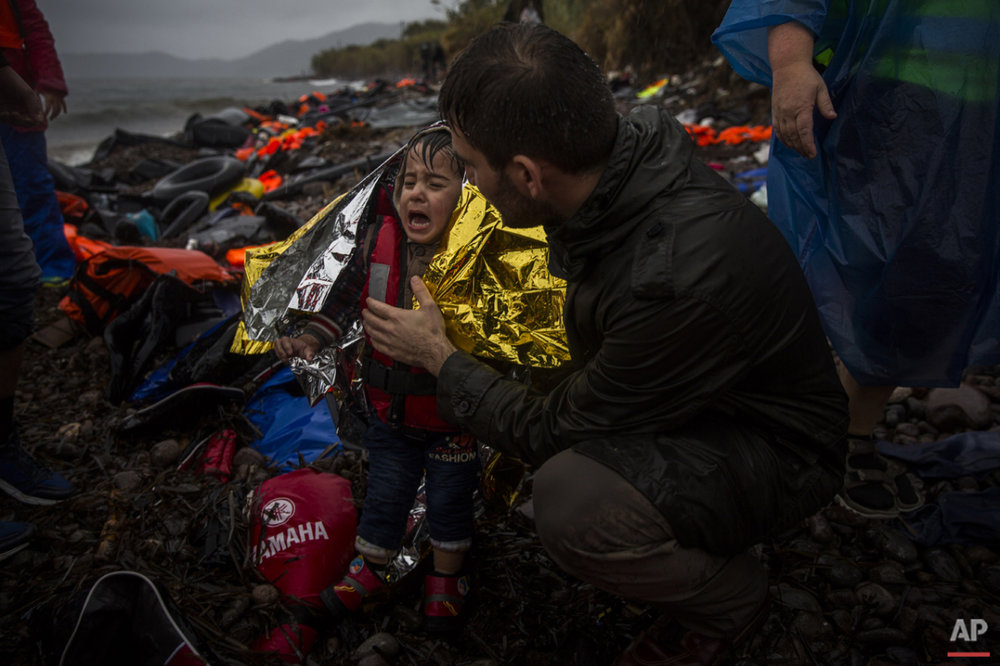 A volunteer tries to calm a child after his arrival with other migrants and refugees on a dinghy from the Turkish coast to the Skala Sykaminias village on the northeastern Greek island of Lesbos, Friday, Oct. 23, 2015. (AP Photo/Santi Palacios)