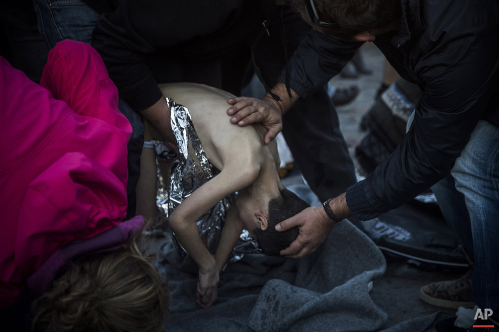Paramedics and doctors try to revive a young boy after a boat with refugees and migrants sank while crossing the Aegean sea from Turkey to the Greek island of Lesbos, on Wednesday, Oct. 28, 2015. The condition of the child is not known. (AP Photo/Santi Palacios)