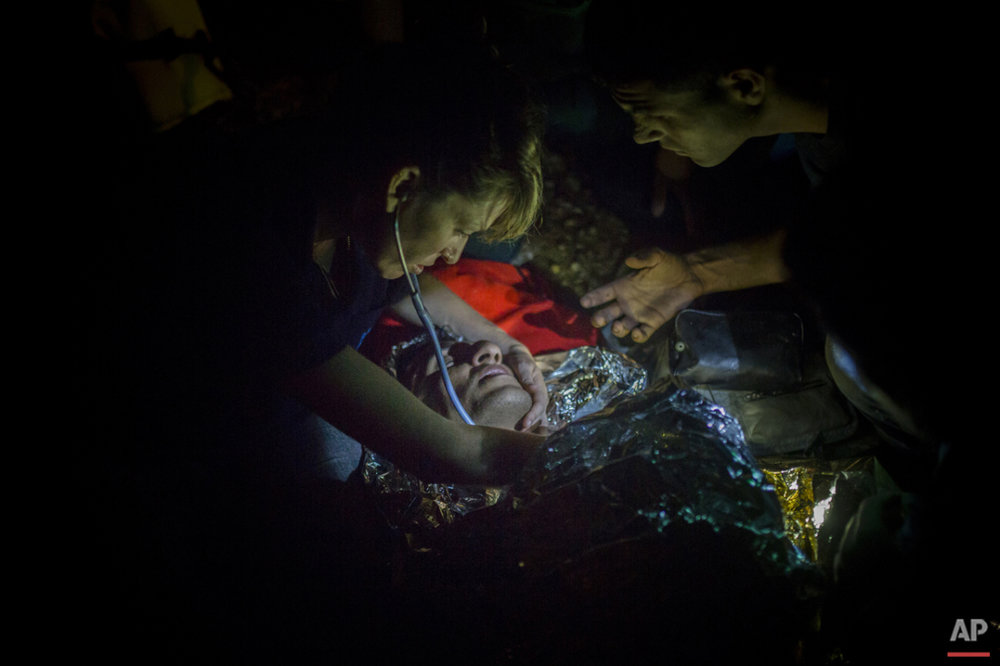 Volunteers provide first aid to a refugee suffering from hypothermia immediately after his arrival on a dinghy from the Turkish coast to the northeastern Greek island of Lesbos, Thursday, Oct. 8, 2015. (AP Photo/Santi Palacios)
