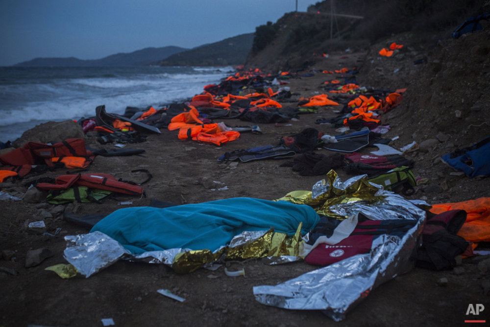 The body of a young man covered with a blue blanket remains on Eftalou beach after his dinghy capsized on the northeastern Greek island of Lesbos, Friday, Oct. 30, 2015. (AP Photo/Santi Palacios)