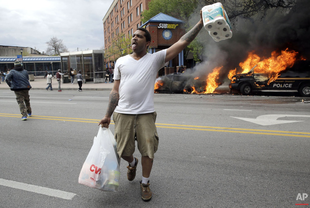 A man carries items that he looted from a store as police vehicles burn, Monday, April 27, 2015, after the funeral of Freddie Gray in Baltimore. (AP Photo/Patrick Semansky)