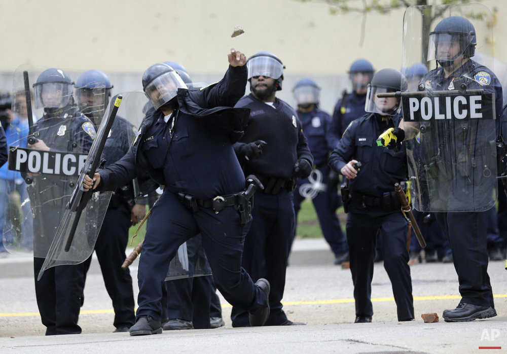 A police officer throws an object at protestors, Monday, April 27, 2015, during unrest following the funeral of Freddie Gray in Baltimore. (AP Photo/Patrick Semansky)