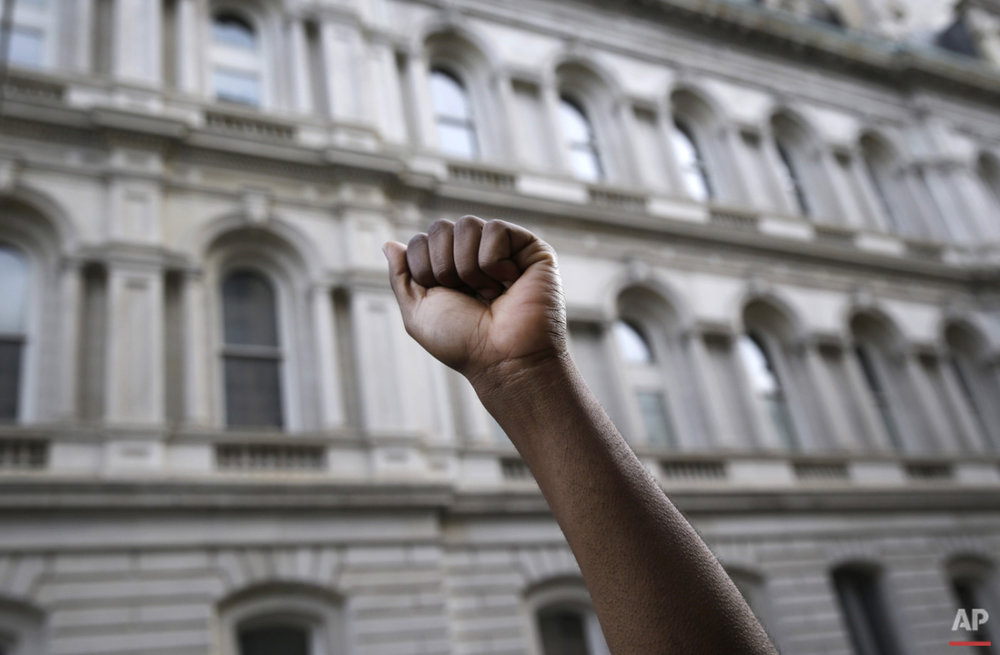 A protestor raises his fist outside of Baltimore City Hall as marchers protest the death of Freddie Gray, Wednesday, April 29, 2015, in Baltimore. (AP Photo/Patrick Semansky)