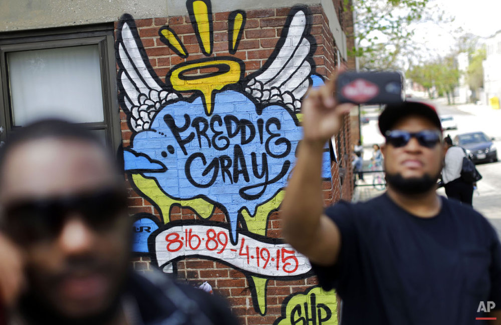 J.R. White, right, takes a selfie in front of a mural that was painted at the site of Freddie Gray's arrest, Saturday, May 2, 2015, in Baltimore, as protesters prepare to march to City Hall. (AP Photo/Patrick Semansky)
