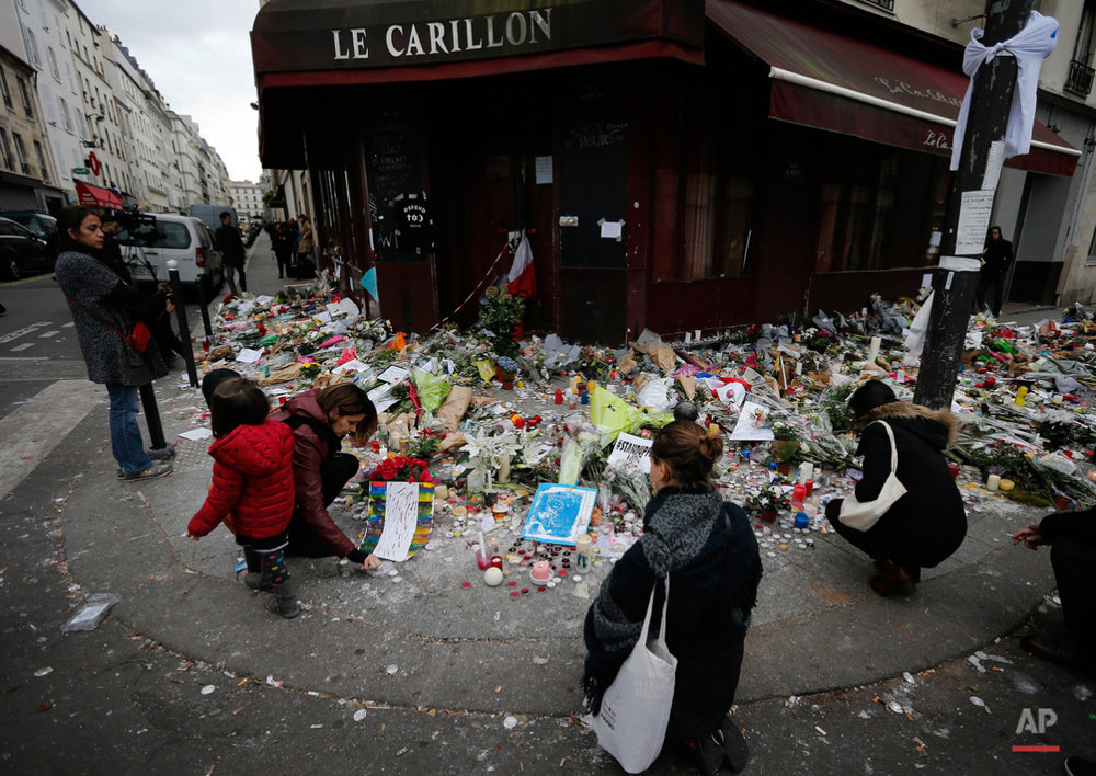 People lay flowers and candles in front of  the restaurant Le Carillon, one of the establishments targeted in Friday's gun and bomb attacks, in Paris, Monday, Nov. 16, 2015. French police raided more than 150 locations overnight as authorities released the names of two more potential suicide bombers involved in the Paris attacksó one born in Syria, the other a Frenchman wanted as part of a terrorism investigation. (AP Photo/Frank Augstein)