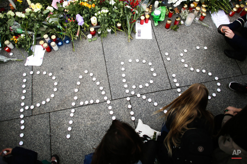 Young women have formed  the word Paris with candles to mourn for the victims killed in  Friday's attacks in Paris, France, in front of the French Embassy in Berlin, Saturday, Nov. 14, 2015. Multiple attacks across Paris on Friday night have left scores dead and hundreds injured.(AP Photo/Markus Schreiber)