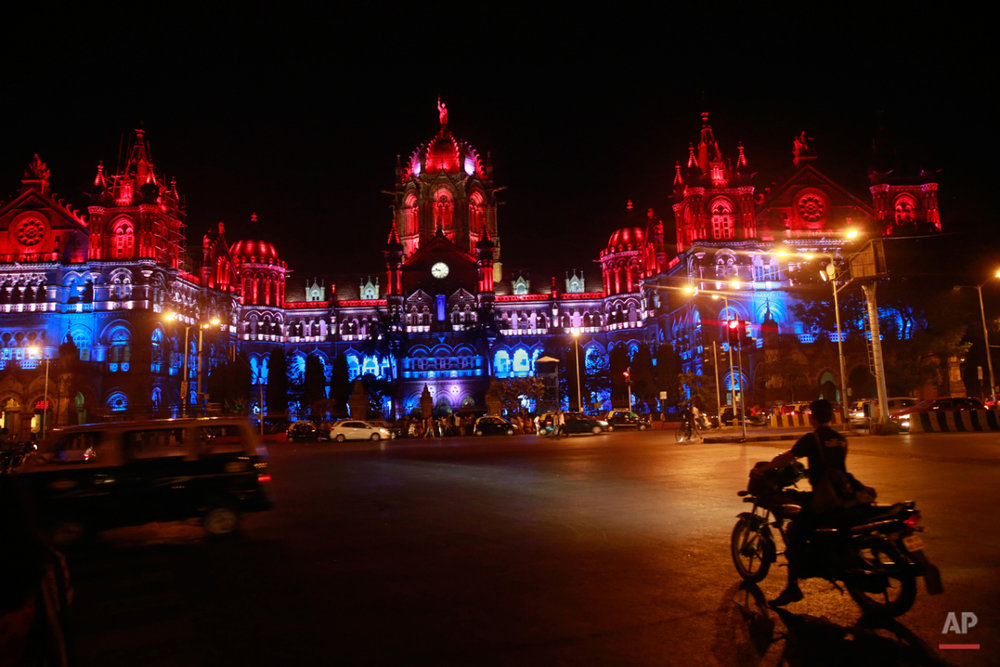 Mumbaiís Chhatrapati Shivaji train station building is illuminated by the colors of the French national flag in solidarity with France following Fridayís Paris terror attacks, Mumbai, India, Sunday, Nov. 15, 2015. This Mumbai landmark was one of the major targets of the 2008 terror attacks that killed 166 people. (AP Photo/Rafiq Maqbool)