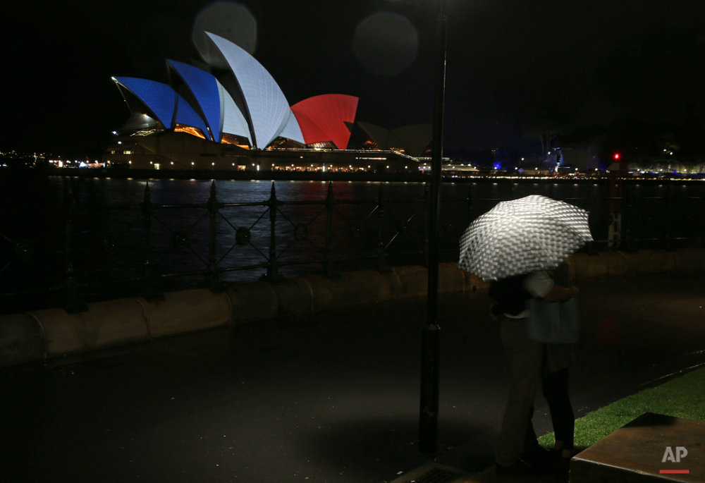 A couple look at the sails of the Sydney Opera House that are lit in the colors of the French flag in Sydney, Saturday, Nov. 14, 2015, following the terrorist attacks in Paris. French police are hunting for possible accomplices of assailants who terrorized Paris concert-goers, cafe diners and soccer fans in the countryÌs deadliest peacetime attacks, a succession of explosions and shootings that cast a dark shadow over this luminous tourist destination. (AP Photo/Rick Rycroft)