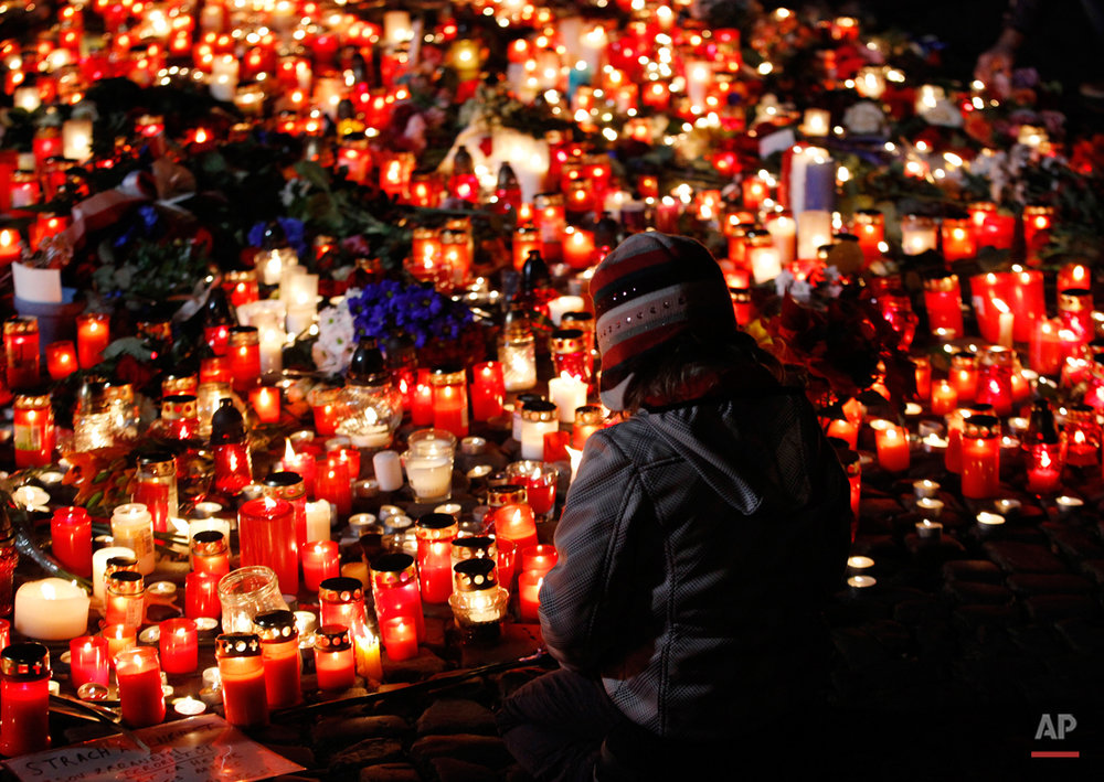 A young girl sits next to flowers and candles placed outside the French embassy in Prague, Czech Republic, Saturday, Nov. 14, 2015, after the attacks in Paris on Friday.  French officials  said scores of people died Friday night when attackers launched gun attacks at Paris cafes, detonated suicide bombs near France's national stadium and killed hostages inside a concert hall during a rock show.   (AP Photo/Petr David Josek)