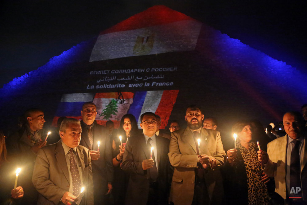 Egyptian tour guides hold a candlelight vigil at the base of the Great Pyramid of Giza in solidarity with victims of attacks in Paris and  Beirut and the Russian plane crash in northern Sinai,  on the outskirts of Cairo, Egypt, Sunday, Nov. 15, 2015. The Islamic State group have claimed responsibility for Friday night's attacks in Paris, Thursdays's twin powerful suicide bombings that tore through a crowded Shiite neighborhood of Beirut, and bringing down a Russian jetliner over Egypt's Sinai region earlier this month. (AP Photo/Thomas Hartwell)