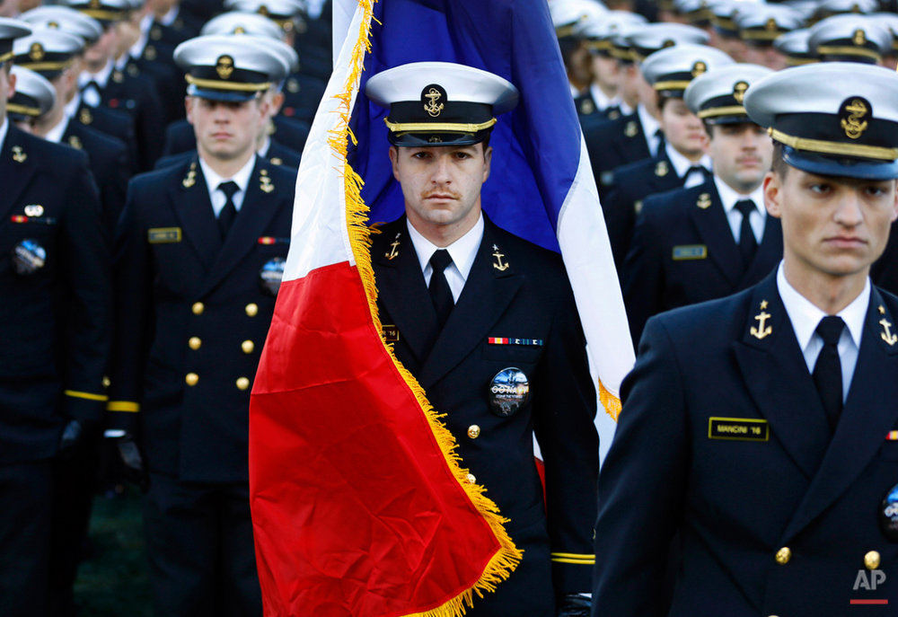 A U.S. Naval Academy midshipman is enveloped by the French national flag as it is caught in a gust of wind before an NCAA college football game between Navy and SMU, Saturday, Nov. 14, 2015, in Annapolis, Md. The brigade of midshipmen marched onto the field with the flag in response to attacks in Paris. (AP Photo/Patrick Semansky)