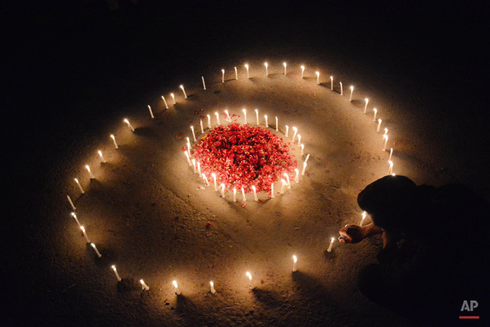 A Pakistani man lights candles during a vigil for victims who were killed in Friday's attacks in Paris, outside French Consulate, in Karachi, Pakistan, Monday, Nov. 16, 2015. Multiple attacks across Paris on Friday night have left scores dead and hundreds injured. (AP Photo/Shakil Adil)