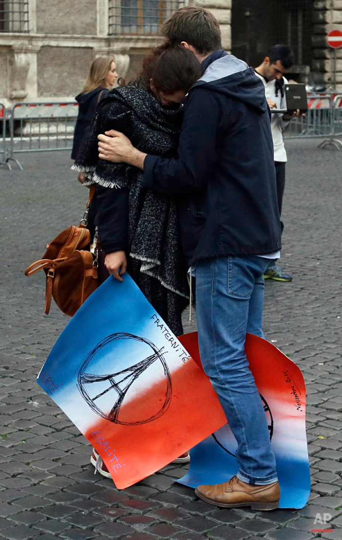 A couple hugs in front of the French embassy in Rome, Saturday, Nov. 14, 2015.  French officials said scores of people died Friday night when attackers launched gun attacks at Paris cafes, detonated suicide bombs near France's national stadium and killed hostages inside a concert hall during a rock show.   (AP Photo/Gregorio Borgia)