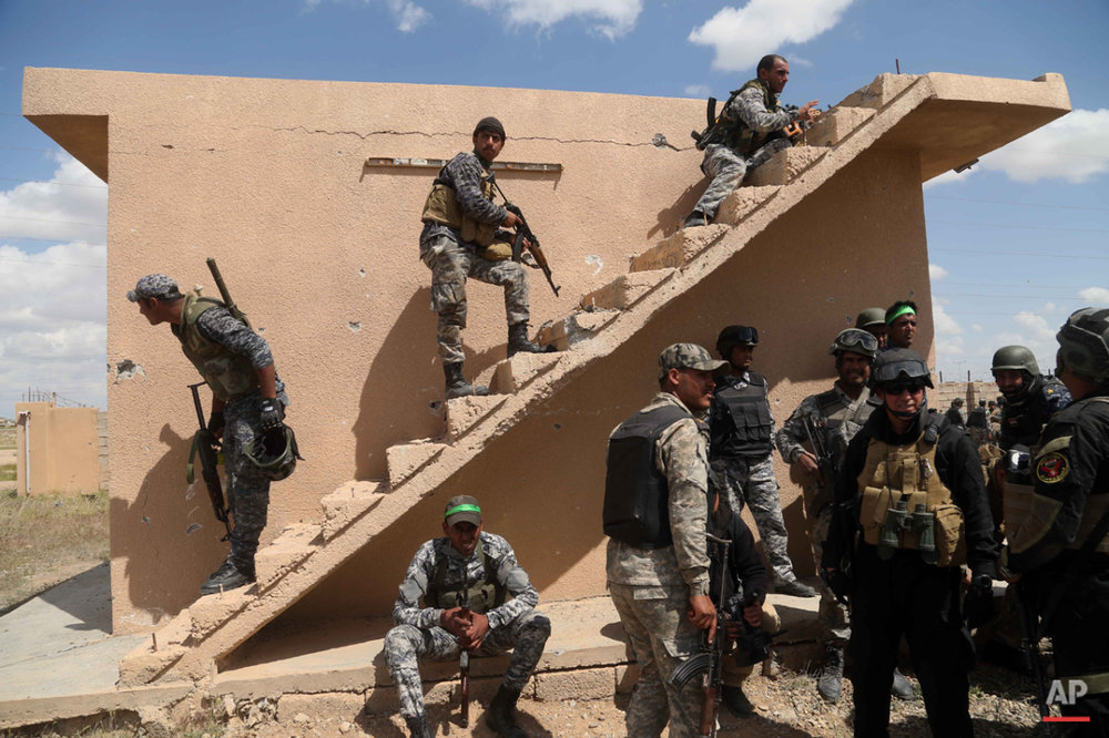 Iraqi security forces and allied Shiite militiamen prepare to attack Islamic State extremists in Tikrit, 80 miles (130 kilometers) north of Baghdad, Iraq, Tuesday, March 31, 2015.  (AP Photo/Khalid Mohammed)