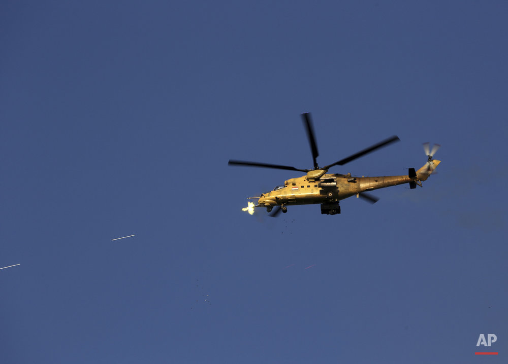 An Iraqi military helicopter attacks Islamic State group positions during clashes in Tikrit, 130 kilometers (80 miles) north of Baghdad, Iraq, Thursday, March 26, 2015. (AP Photo/Khalid Mohammed)