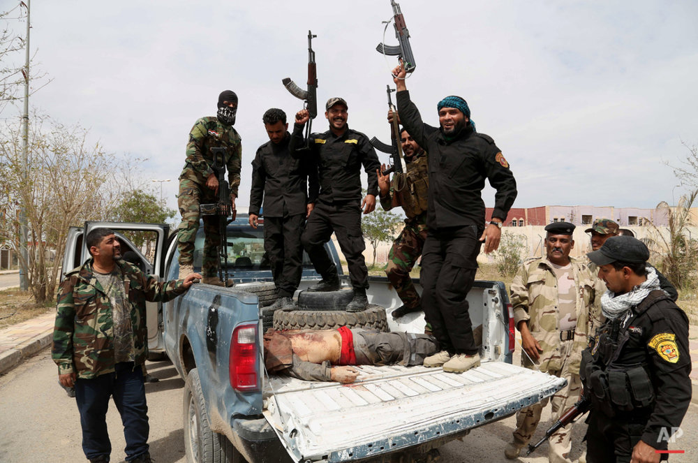 Shiite militiamen chant slogans as they take the body of an Islamic State fighter for burial after overnight clashes in Tikrit, 130 kilometers (80 miles) north of Baghdad, Iraq, Tuesday, March 24, 2015. (AP Photo/Khalid Mohammed)
