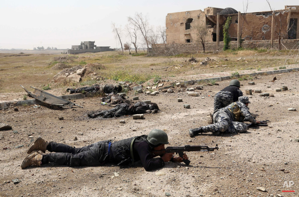 Iraqi security forces attack Islamic State extremists as they take up postions next to bodies of Islamic State fighters in Tikrit, 80 miles (130 kilometers) north of Baghdad, Iraq, Monday, March 30, 2015. (AP Photo/Khalid Mohammed)