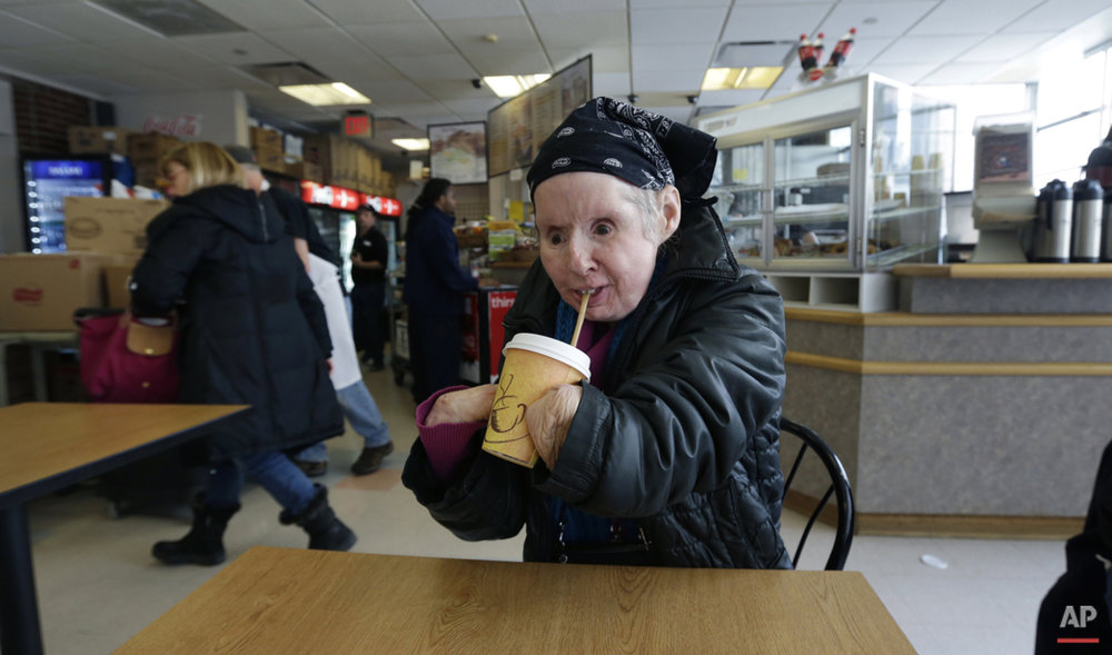 In this Tuesday March 3, 2015 photograph, Charla Nash drinks a cup of hot coffee through a straw while visiting a cafe in Boston.  (AP Photo/Charles Krupa)