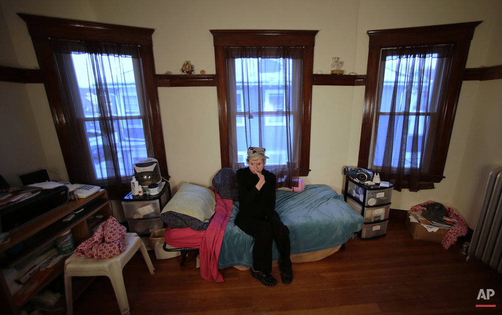 In this Friday, Feb. 20, 2015 photograph, Charla Nash, who is blind, rests in her bedroom between her speakerphone and boom box at her second-story apartment in Boston.  Nash spends much of her time listening to the radio and books on tape. (AP Photo/Charles Krupa)