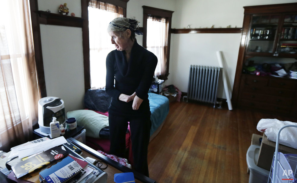 In this Friday, Feb. 20, 2015 photograph, Charla Nash chats with a neighbor on the speakerphone in her bedroom at her second-story apartment in Boston.   (AP Photo/Charles Krupa)