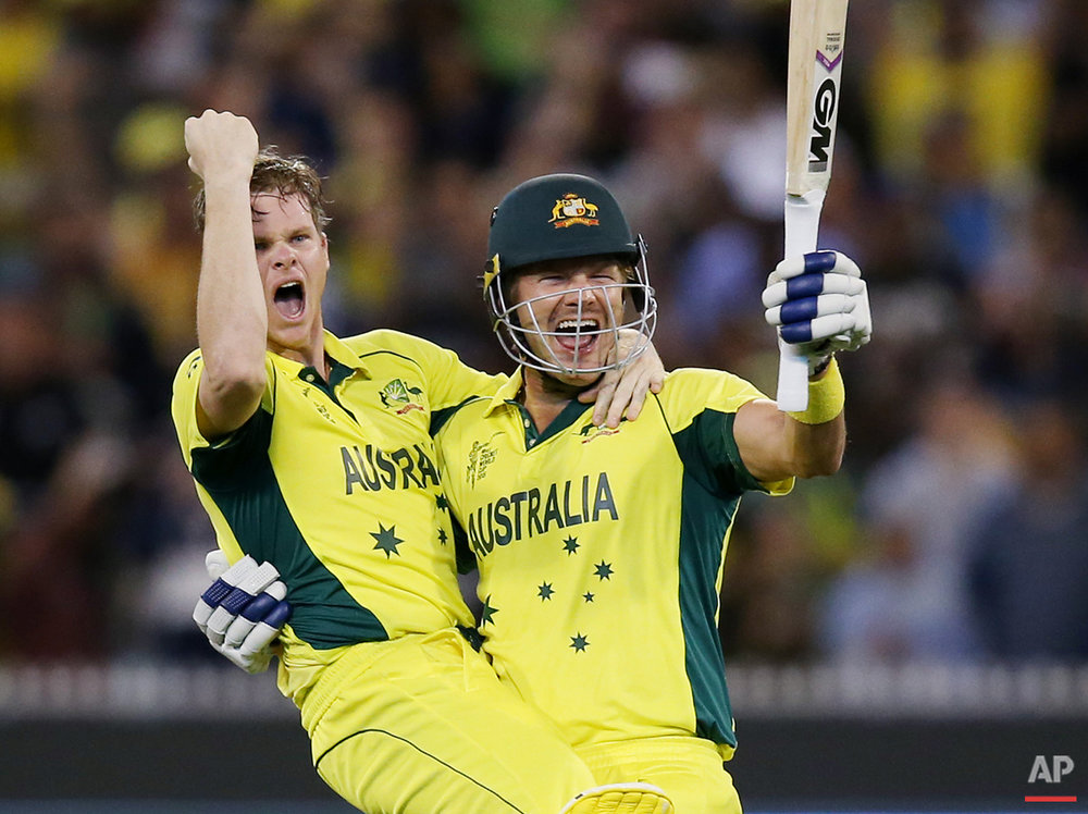Australia's Steve Smith, left, and teammate Shane Watson celebrate after defeating New Zealand by seven wickets to win the Cricket World Cup final in Melbourne, Australia, Sunday, March 29, 2015. (AP Photo/Rick Rycroft)