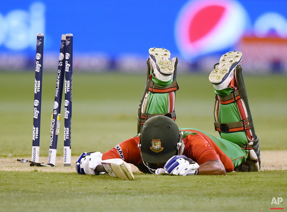 Bangladesh's Imrul Kayes lies on the ground after he was run out for five runs while batting against India during their Cricket World Cup quarterfinal match in Melbourne, Australia, Thursday, March 19, 2015. (AP Photo/Andy Brownbill)