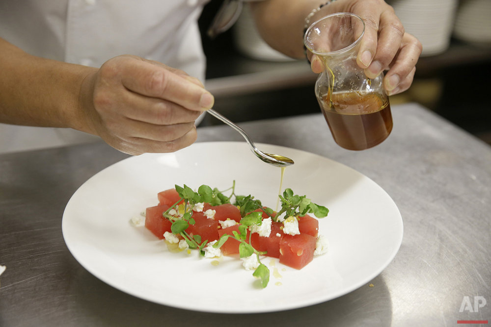 In this photo taken Monday, April 18, 2016, chef Thomas Weibull drizzles honey over a watermelon salad at the Clift Hotel in San Francisco. (AP Photo/Eric Risberg)