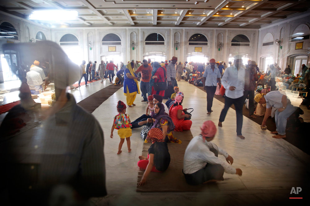 In this May 12, 2015 photo, devotees arrive to have langar at the Bangla Sahib Gurudwara or Sikh temple, in New Delhi, India. The langar, which translates to community meal, begins at noon in a large, high-ceilinged hall at the Bangla Sahib Gurudwara in New Delhi. Several rows of carpets are quickly occupied by people who swarm in and sit down to be served. (AP Photo/Manish Swarup)