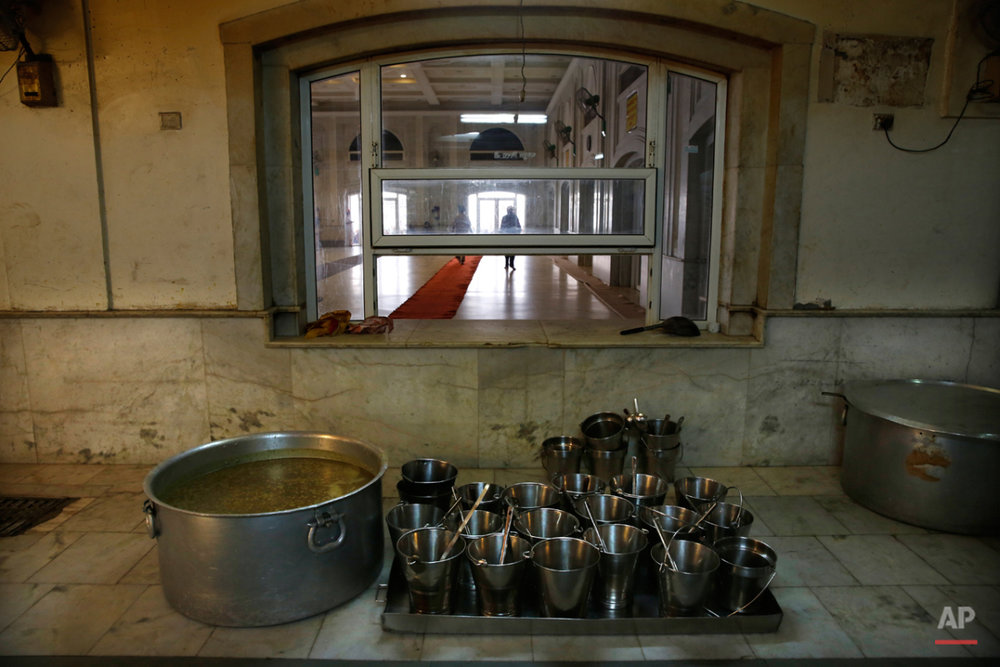 In this May 12, 2015 photo, empty buckets are placed next to a large tub of lentils before the start of langar, which translates to community dinner, at the Bangla Sahib Gurdwara or Sikh temple, in New Delhi, India. Men, women and children throng the kitchen at Bangla Sahib, one of the biggest gurudwara in India, brewing soupy dishes in gigantic metal pots, rolling mounds of dough and flipping breads on mesh-topped stoves. The community meal, which runs into the evening, feeds more than 10,000 people every day. (AP Photo/Manish Swarup)