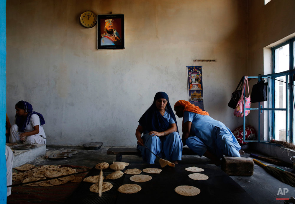 In this June 4, 2015 photo, women prepare Indian breads for langar, which translates to community dinner, for devotees Majnu-ka-Tilla Gurudwara or Sikh temple, in New Delhi, India. Service is one of the most integral traditions of gurudwaras. From cleaning to preparing tons of food every day there is plenty of work to be done. And there are plenty of sevadaars, or volunteers, to do it.  (AP Photo/Manish Swarup)