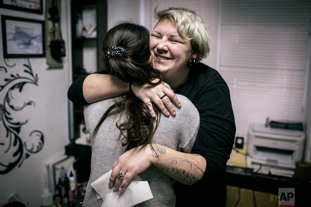 In this photo taken on Tuesday, Dec. 6, 2016, tattoo artist Yevgeniya Zakhar hugs a woman she gave a tattoo to conceal a scar from a domestic violence attack, in Ufa, Russia. Yevgeniya Zakhar, a Russian tattoo artist from Ufa, a city about 1,200 kilometers (745 miles) east of Moscow, gives free tattoos to victims of domestic abuse, to cover their scars. The upper chamber of the Russian parliament last week passed a controversial bill decriminalizing some forms of domestic violence. (AP Photo/Vadim Braydov)