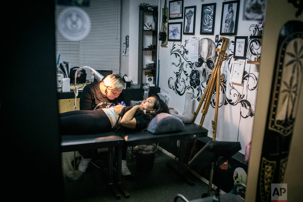In this photo taken on Monday, Dec. 5, 2016, tattoo artist Yevgeniya Zakhar works with a client, a victim of domestic violence, in Ufa, Russia. Yevgeniya Zakhar, a Russian tattoo artist from Ufa, a city about 1,200 kilometers (745 miles) east of Moscow, gives free tattoos to victims of domestic abuse, to cover their scars. The upper chamber of the Russian parliament last week passed a controversial bill decriminalizing some forms of domestic violence. (AP Photo/Vadim Braydov)