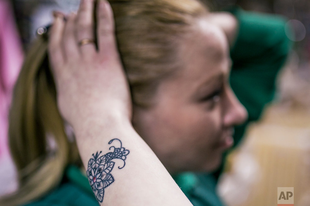 In this photo taken on Wednesday, Feb. 1, 2017, Katarina Golovkova shows a tattoo she had done over the scars from a domestic violence attack she sustained five years earlier in Ufa, Russia. Yevgeniya Zakhar, a Russian tattoo artist from Ufa, a city about 1,200 kilometers (745 miles) east of Moscow, gives free tattoos to victims of domestic abuse, to cover their scars. The upper chamber of the Russian parliament last week passed a controversial bill decriminalizing some forms of domestic violence. (AP Photo/Vadim Braydov)